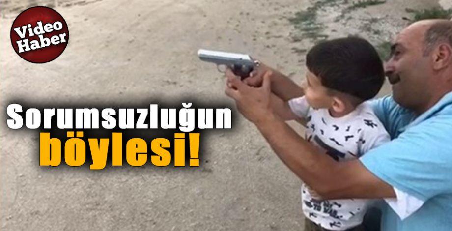 Çocuğunun eline silah verip ateş ettirdi