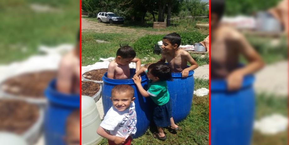 Sıcaktan bunalan çocuklar su dolu varillerde serinliyor